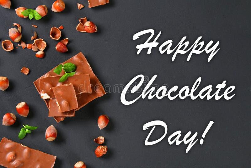 巧克力用榛子、咖啡薄菏和五谷在一张深灰桌上的 顶视图 7月11日是天巧克力 免版税图库摄影