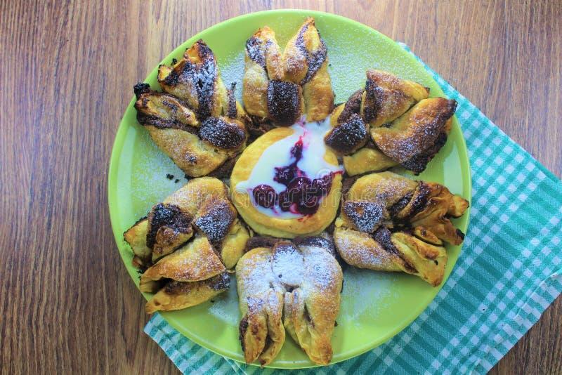 巧克力矿块油酥点心花用用搽粉的糖,绿色和棕色木bac和酸樱桃盖的香草调味汁 库存图片