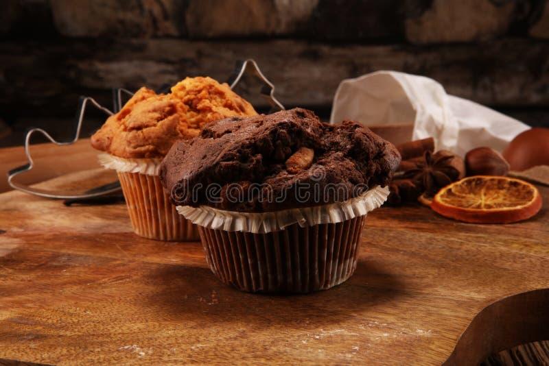 巧克力碎片松饼和坚果松饼,自创面包店木backgrou 免版税库存照片
