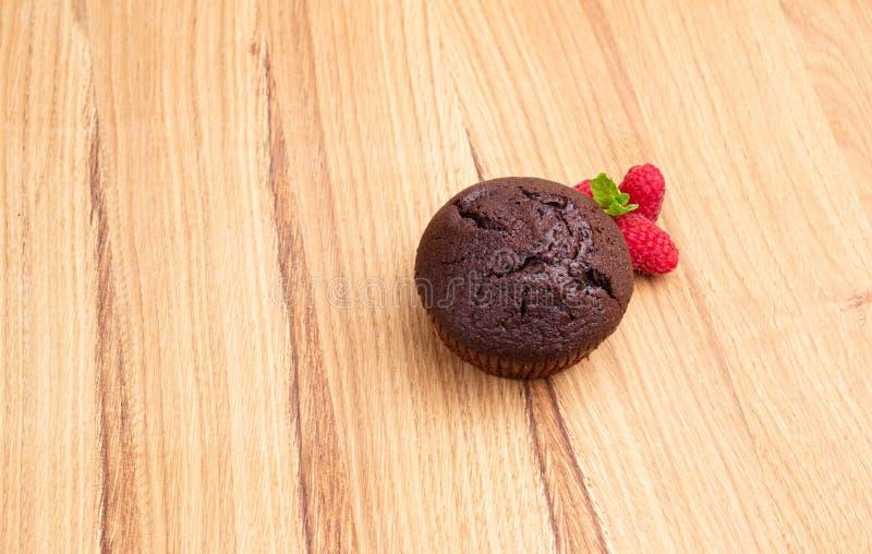 巧克力碎片松饼用在一张轻的木桌上的莓莓果 与圆点的餐巾 免版税库存图片