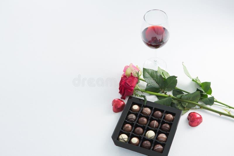 巧克力箱子、玫瑰和红葡萄酒玻璃在白色背景 库存图片