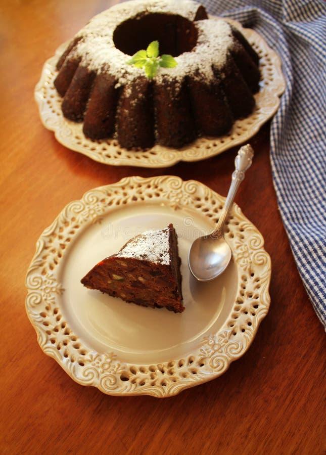 巧克力腹网蛋糕洒与果子,在板材白色背景的糖粉末 库存图片