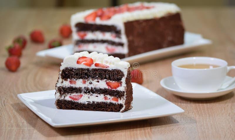 巧克力草莓片断在有一杯茶的白色板材结块 库存图片