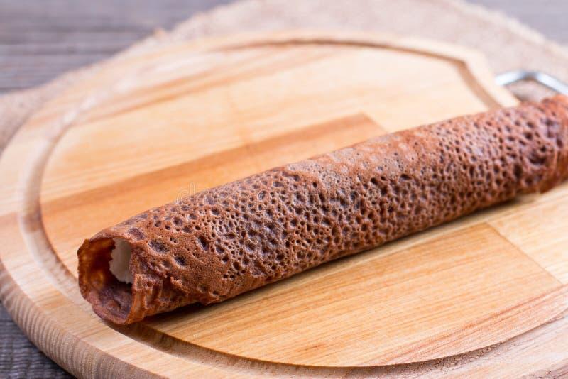 巧克力薄煎饼滚动用凝乳和果子准备好全家的早餐 免版税库存照片