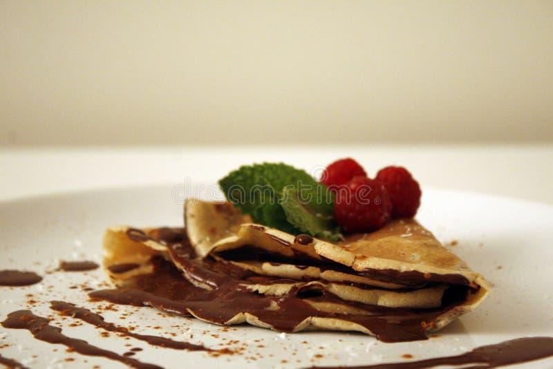 巧克力薄煎饼用莓和薄荷的叶子 免版税库存图片
