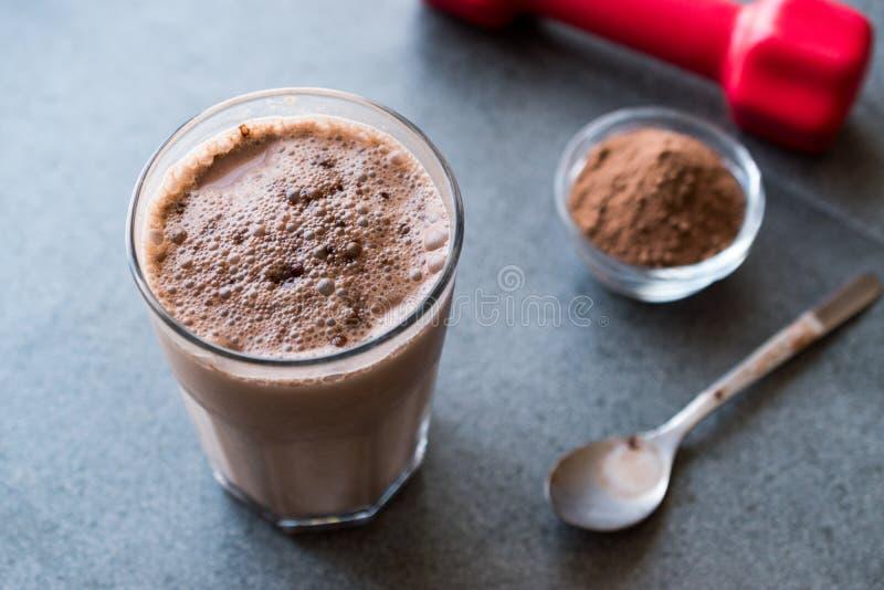 巧克力蛋白质与乳清蛋白粉末和红色哑铃的震动圆滑的人 免版税库存图片