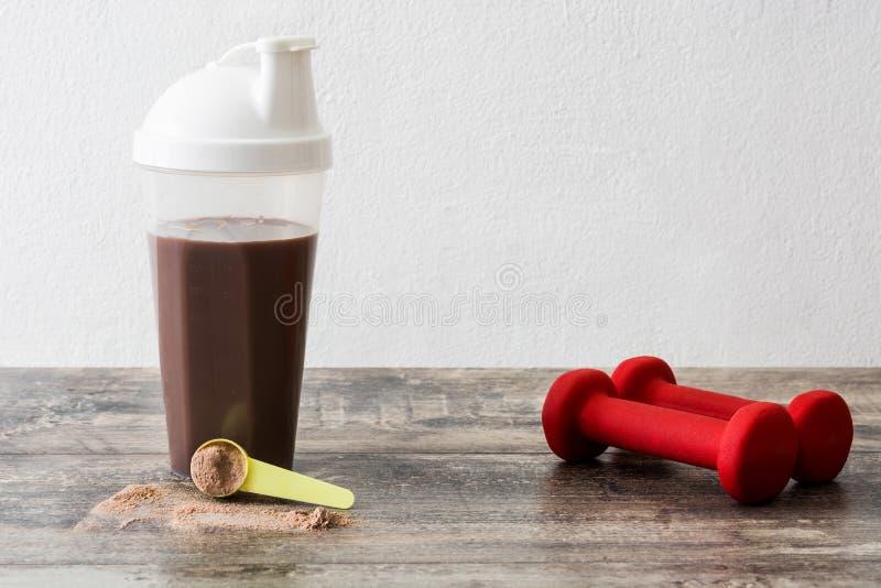 巧克力蛋白质震动和哑铃 免版税库存照片