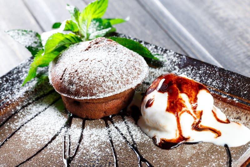 巧克力蛋糕或方旦糖与香草冰淇淋球在黑暗的木背景 库存图片