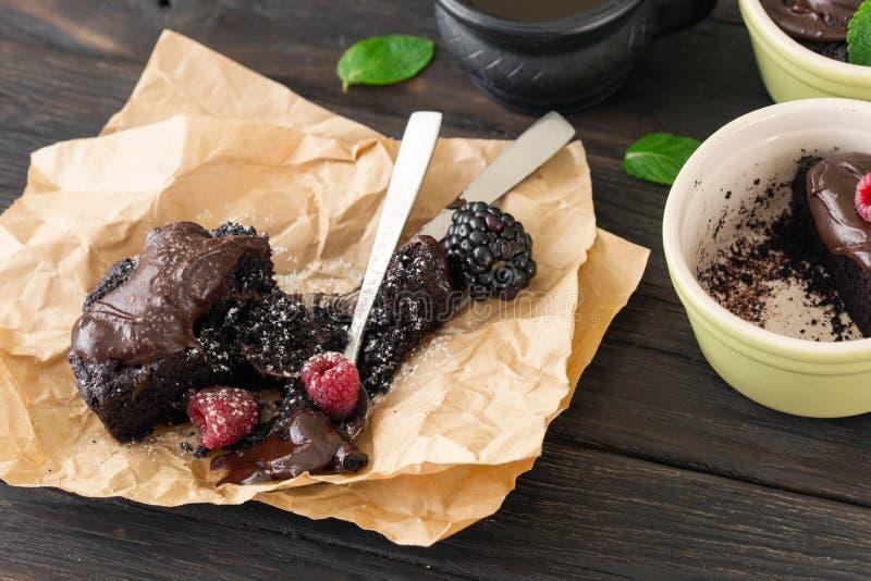 巧克力蛋糕用在一张黑暗的木桌上的莓果 免版税库存图片