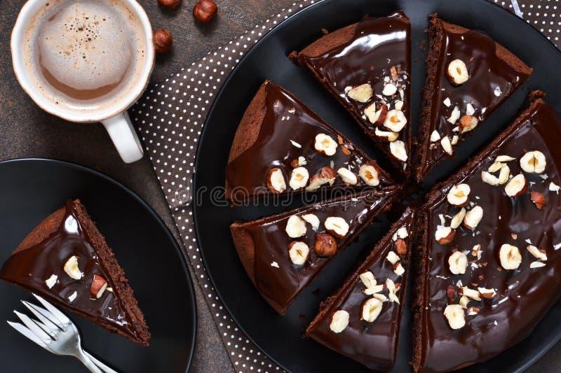 巧克力蛋糕用巧克力热饮调味汁和油煎的榛子 免版税库存照片
