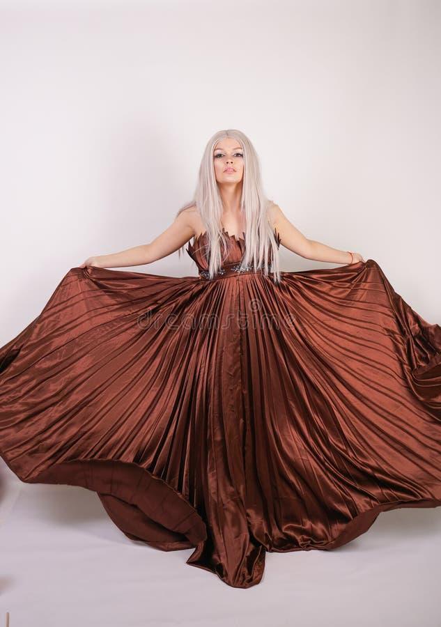 巧克力颜色长的晚礼服的豪华白肤金发的白种人模型女孩挥动一件飞行的礼服的做了被打褶的织品并且站立o 免版税库存图片