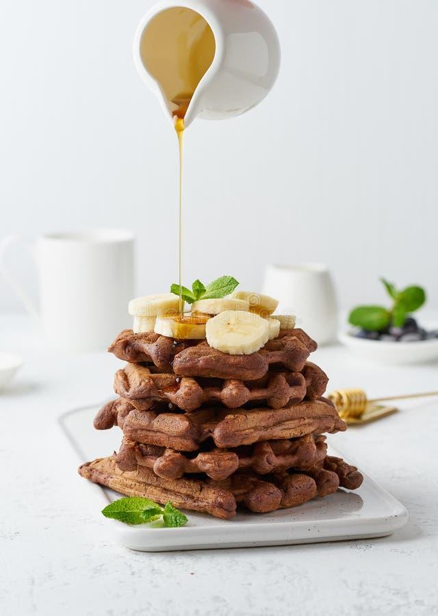 巧克力香蕉在白色桌,侧视图,垂直上胡扯 甜早午餐,在牛奶罐,盛奶油小壶的枫蜜流程 库存照片
