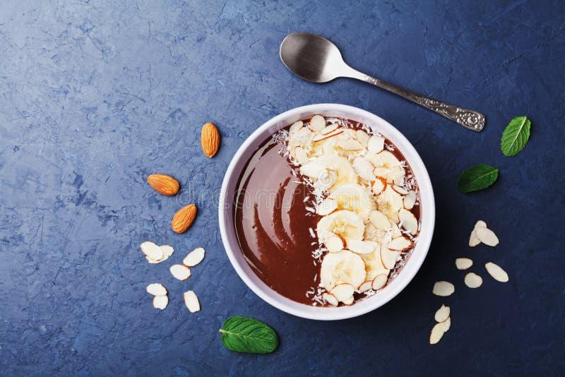 巧克力香蕉杏仁椰子在蓝宝石台式视图的圆滑的人碗 健康早餐或点心 平的位置 免版税库存照片
