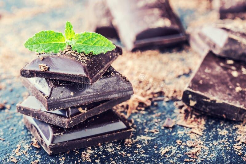 巧克力 黑色巧克力 黑巧克力一些个立方体与薄荷叶的 免版税库存照片