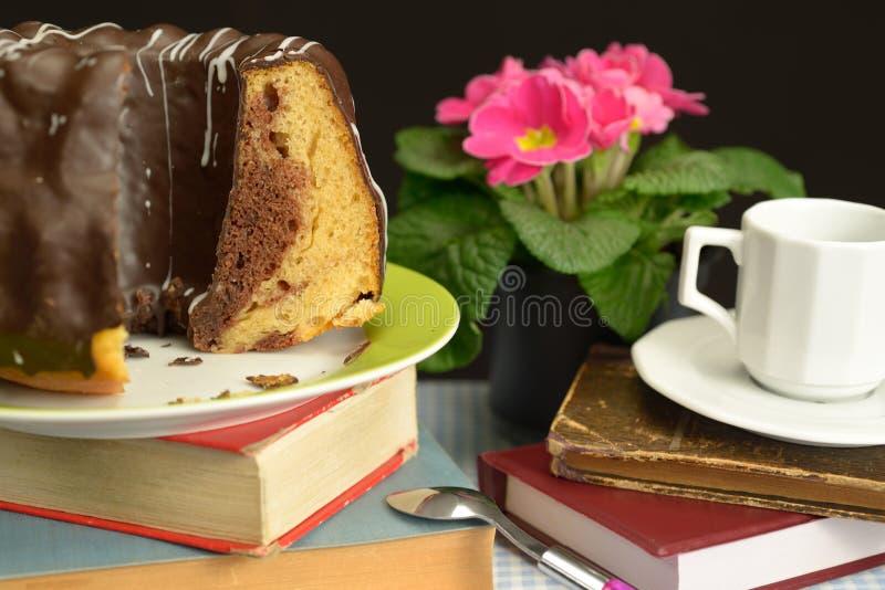 巧克力Gugelhupf旧书变粉红色花杯匙子 库存图片