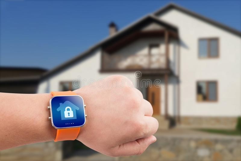 巧妙的手表以在一只手上的住家安全app在大厦背景 免版税库存照片