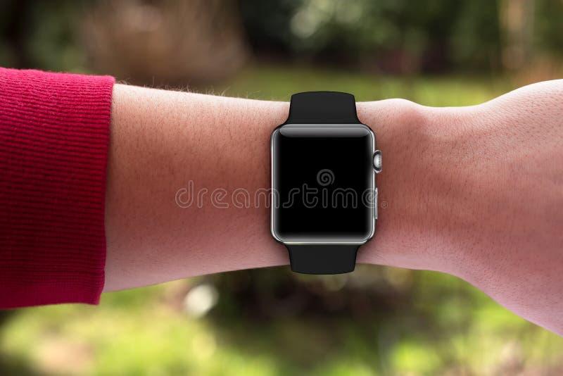 巧妙的手表在手边有黑带和黑屏的 库存照片