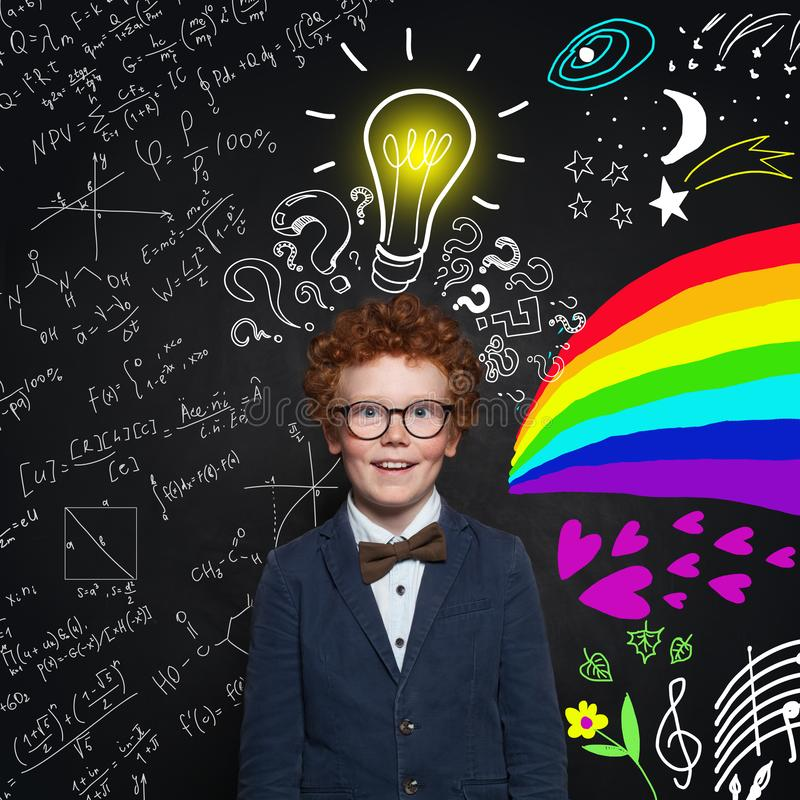 巧妙的滑稽的小男孩戴着眼镜和蓝色衣服在背景与问号,电灯泡,问号 免版税图库摄影