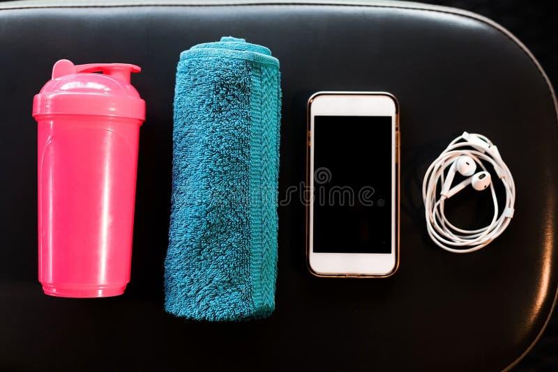 巧妙的电话、耳机、毛巾和一台振动器在一条长凳在健身房 图库摄影
