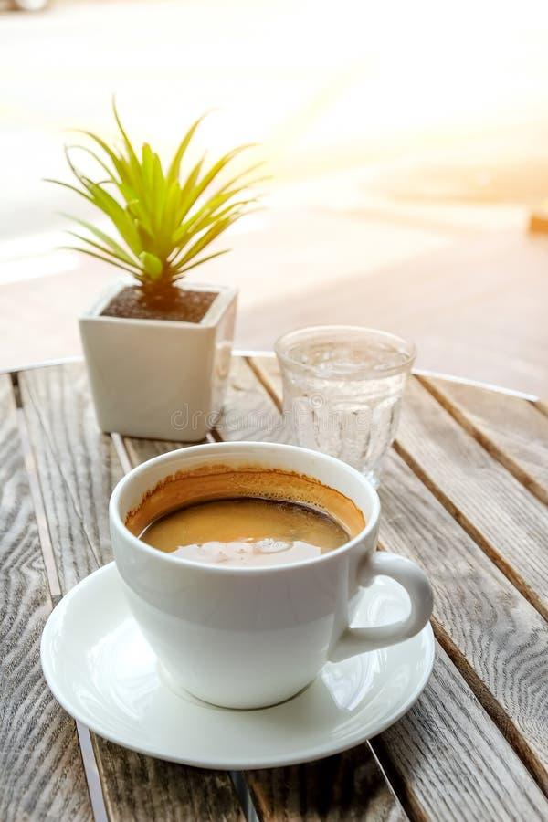 巧妙的电话和加奶咖啡杯子用在木的玻璃水 免版税库存图片