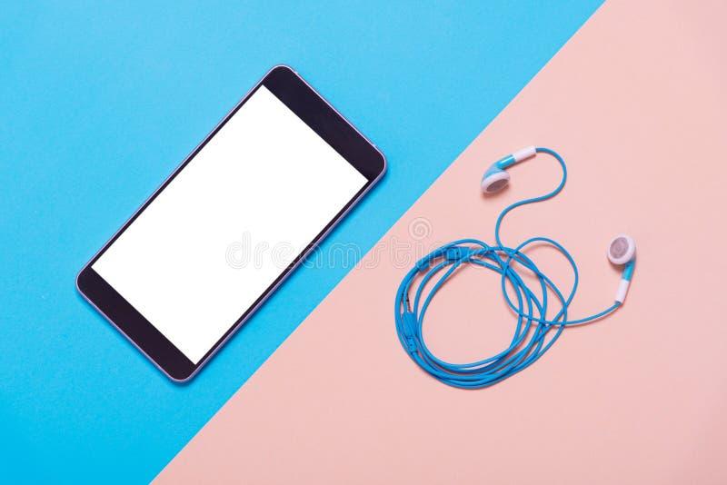 巧妙的电话和耳机平的位置在颜色纸,最小的s 免版税库存照片