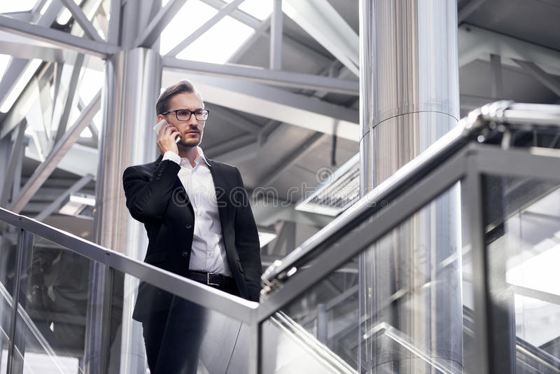 巧妙的电话的人-年轻商人在机场 穿衣服夹克的镜片的英俊的严肃的人户内 免版税库存照片
