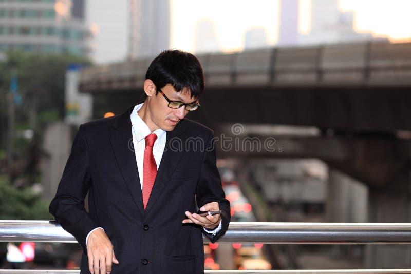 巧妙的电话的人-年轻商人 使用智能手机微笑的愉快的外部办公室修造的偶然都市专业商人 免版税库存图片