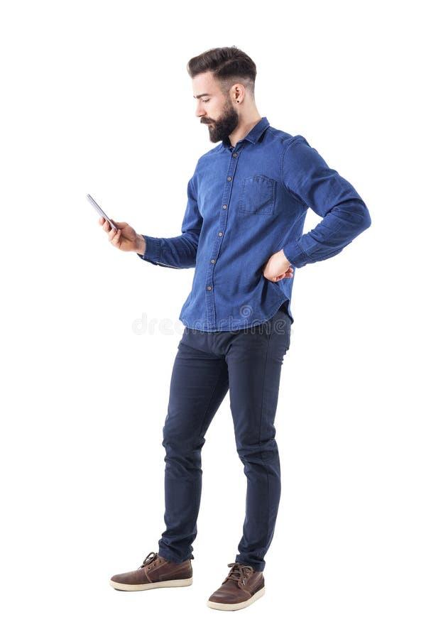巧妙的电话的年轻英俊的穿着体面的商人冲浪的互联网 侧视图 免版税库存照片