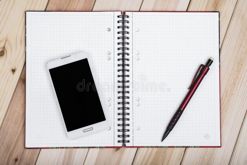 巧妙的电话,在书桌上的笔记本 库存图片