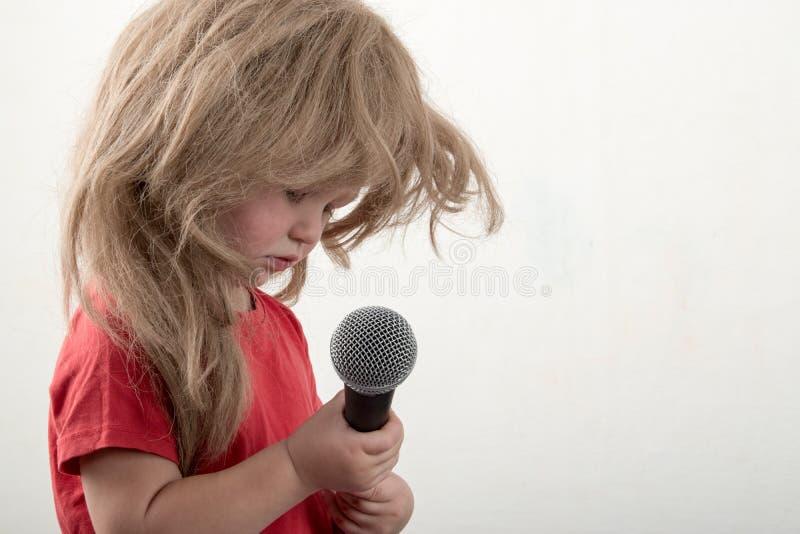 巧妙的衣裳的两个愉快的小男孩在家唱与话筒的一首歌曲 为圣诞节卡拉OK演唱做准备 图库摄影