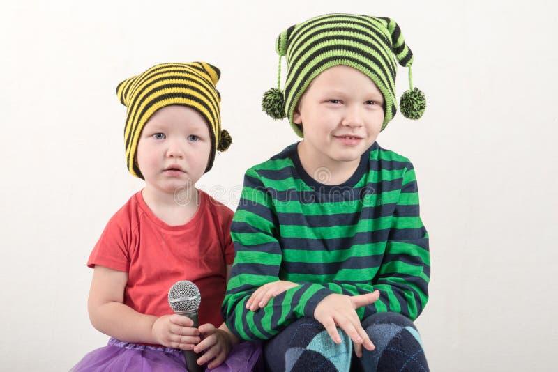 巧妙的衣裳的两个愉快的小男孩在家唱与话筒的一首歌曲 为圣诞节卡拉OK演唱做准备 库存照片