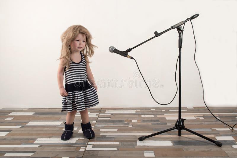 巧妙的衣裳的愉快的小男孩在家唱与话筒的一首歌曲 为圣诞节卡拉OK演唱做准备 免版税库存照片