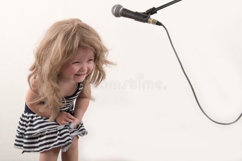 巧妙的衣裳的愉快的小男孩在家唱与话筒的一首歌曲 为圣诞节卡拉OK演唱做准备 免版税库存图片