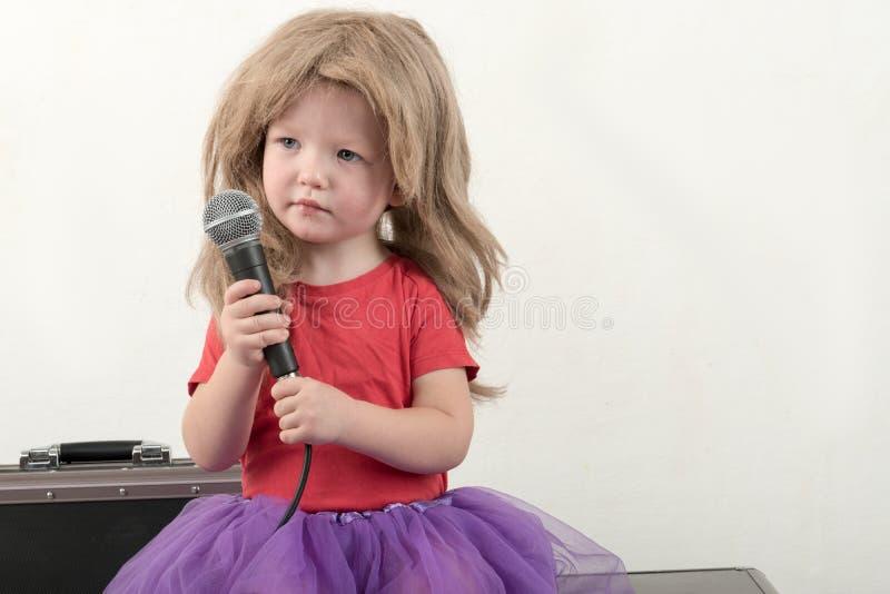 巧妙的衣裳的愉快的小男孩在家唱与话筒的一首歌曲 为圣诞节卡拉OK演唱做准备 库存照片