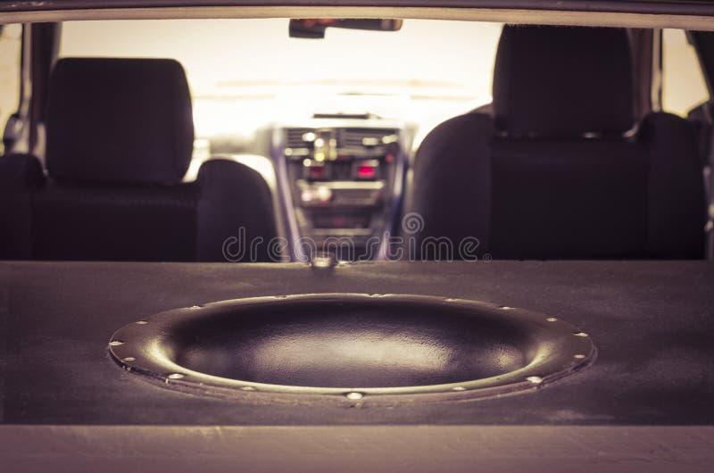 巨型在树干的超低音扬声器合理的报告人 被弄脏的汽车内部 免版税库存图片