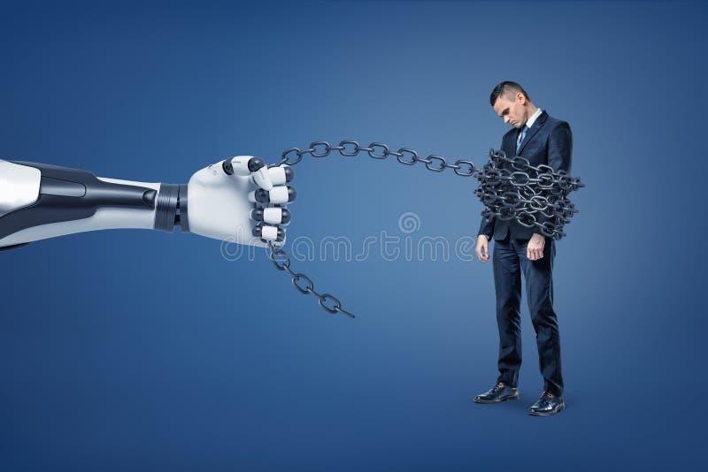 巨型机器人手拉扯在与它捉住的一个哀伤的商人的一个金属链子 免版税库存照片