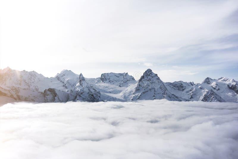 巨型的多雪的山的巨大看法 在云彩上的惊人的冬天岩石 免版税库存图片