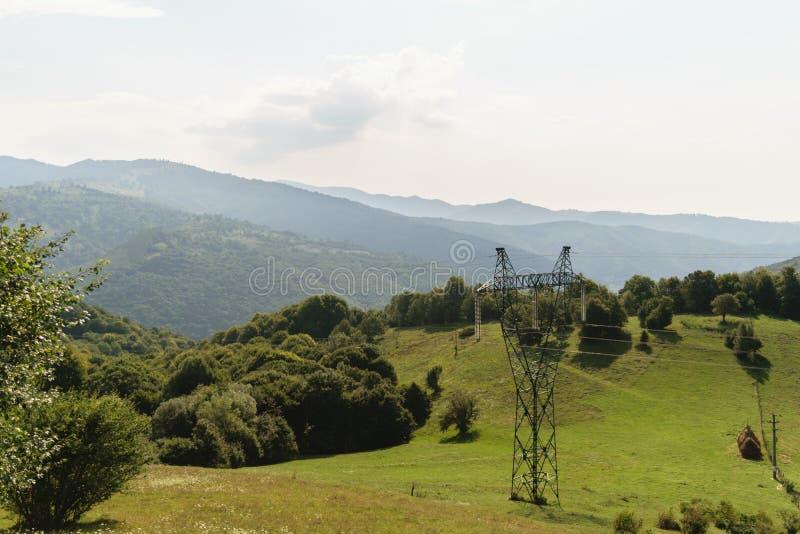 巨型的电杆本质上,绿色植被在背景中盖了山 高压电柱子 免版税库存图片