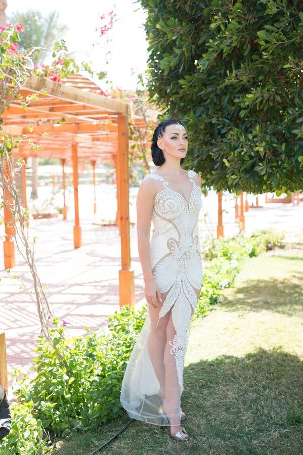 巨大查找 妇女做发型穿有刺绣和珍珠的时兴的紧身礼服 豪华的夫人 免版税库存图片