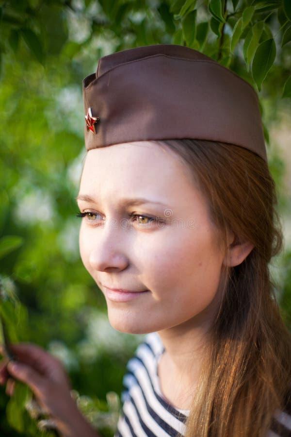 巨大爱国战争的制服的女孩 战士坐在花之间的草 穿世界大战的绿色服装女孩 免版税库存图片