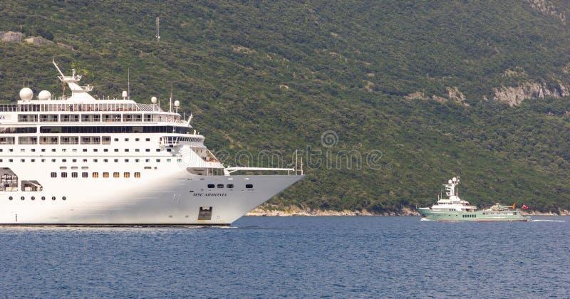 巨大的乘客游轮和一条小私有马达游艇有一个停机坪的在博卡队Kotorska海湾 图库摄影