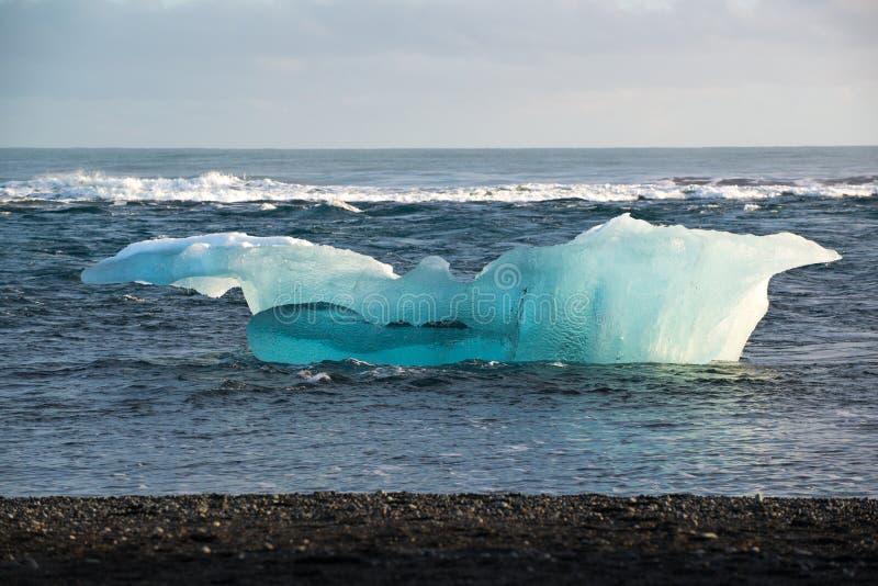 巨大的冰山在海洋,在Jokulsarlon,冰岛的黑沙子海滩 免版税库存照片