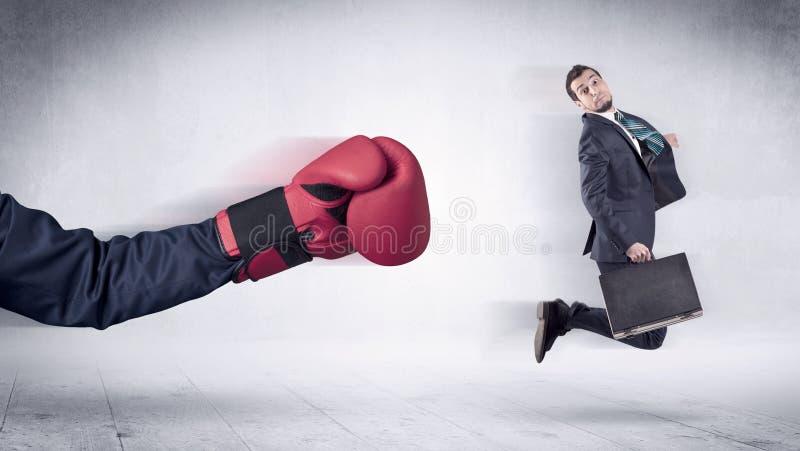 巨大的拳击手套拳打商人概念 库存照片