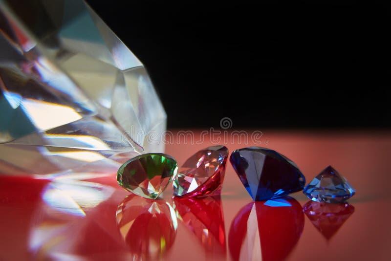 巨大的金刚石和几别致的水晶红色和黑表面、淡光和闪闪发光上 免版税库存图片
