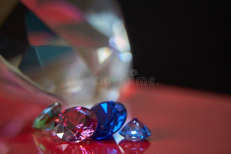 巨大的金刚石和几别致的水晶红色和黑表面、淡光和闪闪发光上 免版税图库摄影