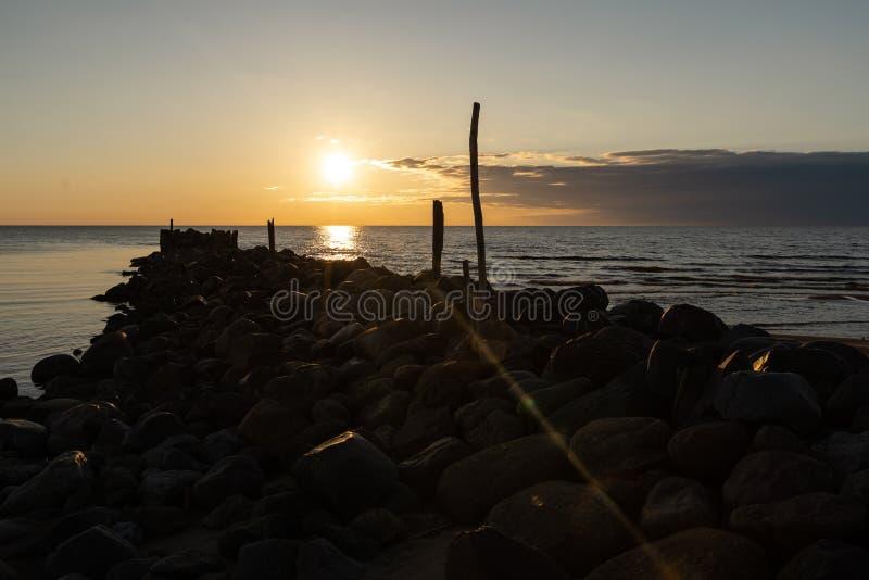 巨石城海滩与生动的红色和橘黄色的码头日落在波儿地克的海Tuja,拉脱维亚- 2019年4月13日 库存图片