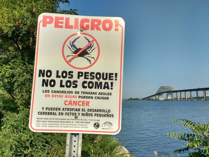 巨蟹星座警告,危险螃蟹,纽瓦克海湾桥梁,西班牙语标志 库存照片