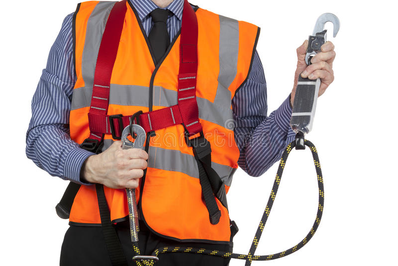 巩固安全带短绳的橙色可见性背心的大厦测量员 库存照片