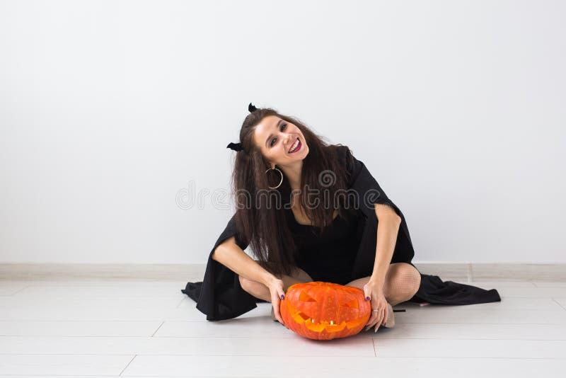 巫婆万圣节服装的愉快的哥特式年轻女人微笑在绝尘室背景的 免版税图库摄影