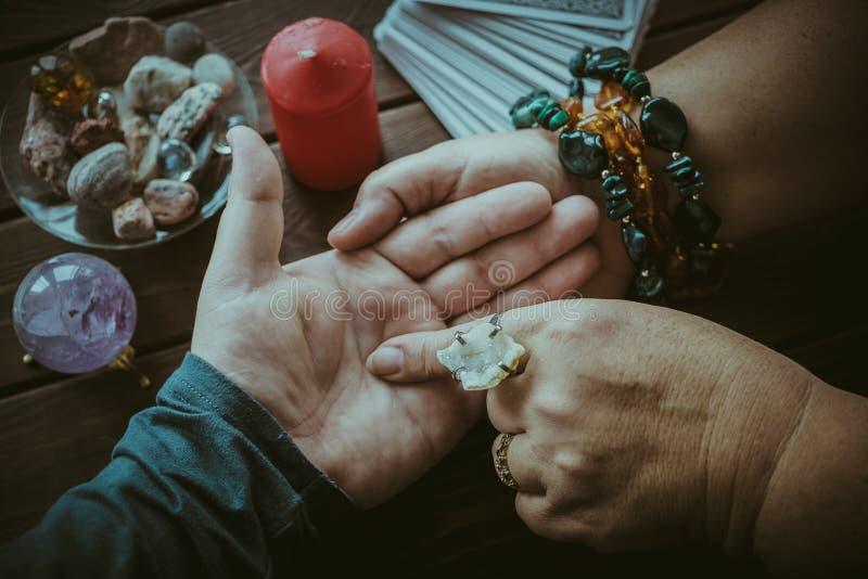 巫婆或算命者读书时运在男性棕榈或手排行 免版税库存图片